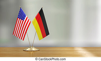 American and German flag pair on a desk over defocused background