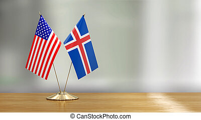 American and Icelandic flag pair on a desk over defocused background