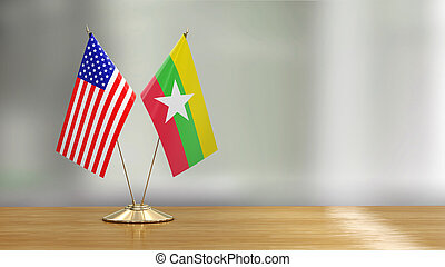 American and Myanmar flag pair on a desk over defocused background