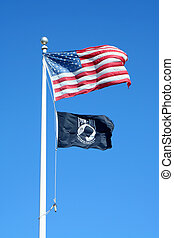 American and POW flags against a blue sky - A American and...
