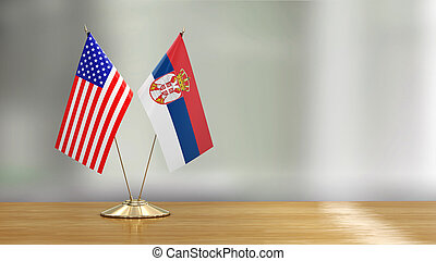 American and Serbian flag pair on a desk over defocused background