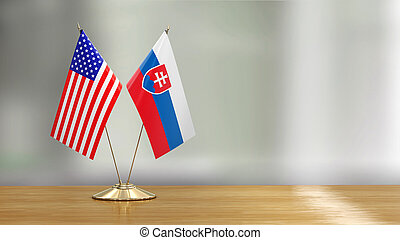 American and Slovak flag pair on a desk over defocused background