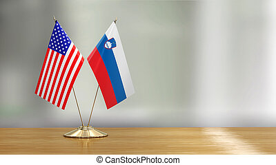 American and Sloven flag pair on a desk over defocused background