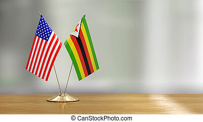 American and Zimbabwe flag pair on a desk over defocused background
