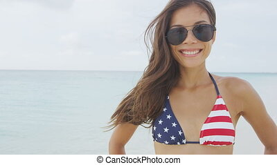 American woman portrait smiling on beach vacation wearing aviator sunglasses and USA flag bikini fashion swimwear. Stars and stripes pattern united states style.