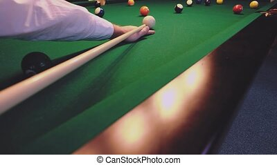 American billiard. Man playing billiard, snooker. Player preparing to shoot, hitting the cue ball.