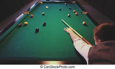 American billiard. Man playing billiard, snooker. Player preparing to shoot, hitting the cue ball. Ball going into the hole. A simple blow from close range.