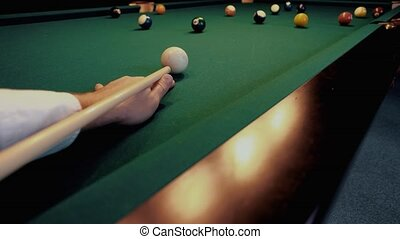 American billiard. Man playing billiard, snooker. Player preparing to shoot, hitting the cue ball. Ball number one 1 going near the hole. A misfire from close range.