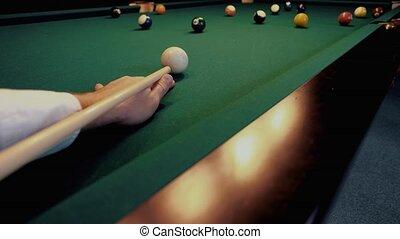 American billiard. Man playing billiard, snooker. Player preparing to shoot, hitting the cue ball.