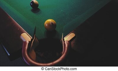 American billiard. Man playing billiard, snooker. Player preparing to shoot, hitting the cue ball. Ball number one 1 going into the hole. A simple blow from close range.