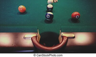 American billiard. Man playing billiard, snooker. Player training to shoot, hitting the cue ball. Ball number ten 10 going into the hole