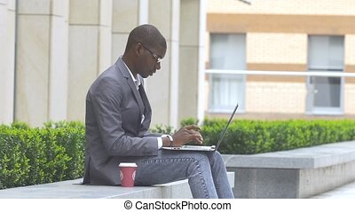 american businessman working with glasses on laptop outdoors on a background of corporate building