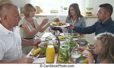 American caucasian family having dinner at desk in home kitchen interior.