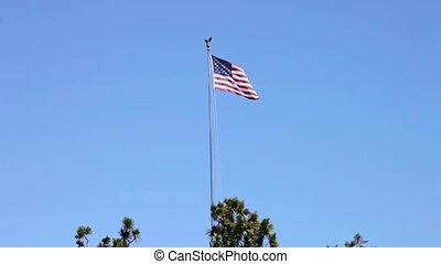 National cemetery with American flag waving. San Francisco Bay at National Cemetery Presidio, California, United States. Copy space with blue sky.