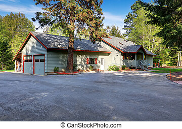 American country house exterior with wide asphalt driveway .