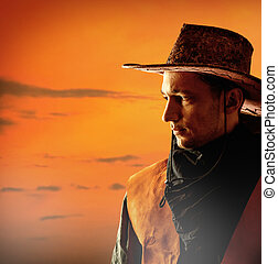 American cowboy in brown hat on a sunset background outdoor