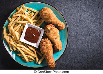 American cuisine - French fries and fried chicken legs on...