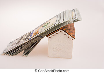 American dollar banknotes on the roof of a model house
