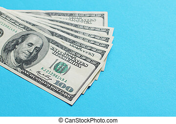 American dollars in bills of one hundred dollars on a blue background.