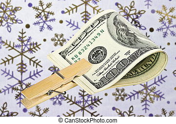 American dollars with a clothespin on the background of snowflak