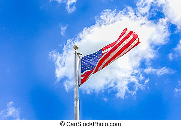 American flag against a blue sky with white clouds