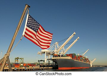 An American flag waves in the foreground at this US port, where a cargo ship loaded with containers is berthed beneath giant cranes on a clear blue sky day. The image symbolizes concepts like Made in America, Made in the USA, industry, global economy, pride, strength, power, patriotism, trade, ...