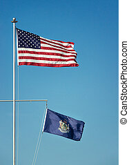 American flag and the State flag of Maine against blue sky