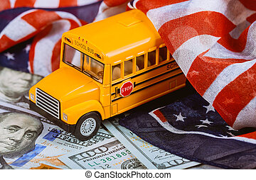 American flag and US banknotes dollar cash money and school bus
