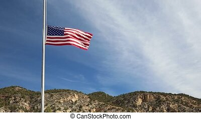 american flag at half-mast blowing in the wind