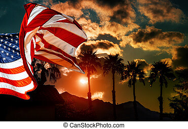 American flag at palm tree silhouette on a background of tropical sunset
