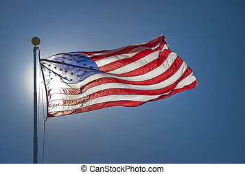 American flag back lit by sun