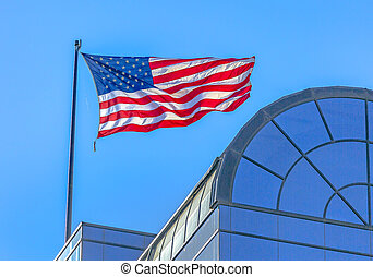 American flag blowing in the wind on building