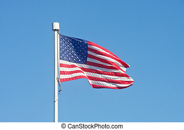 An American flag blowing in the wind on a flagpole in a clear blue sky