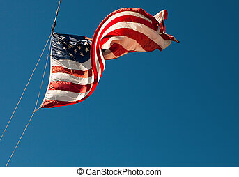 American flag blowing in the wind on the blue sky