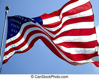 American Flag flapping in the wind against a blue sky