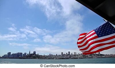 American flag in San Francisco Bay cityscape. Tour to Alcatraz island by ferry boat waving in San Francisco pier with cityscape. Cloudy sky. San Francisco, California, United States