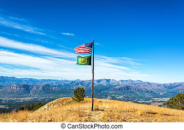 American and Forest Service flags flying above a dramatic mountainous landscape near Yellowstone National Park in Wyoming, USA