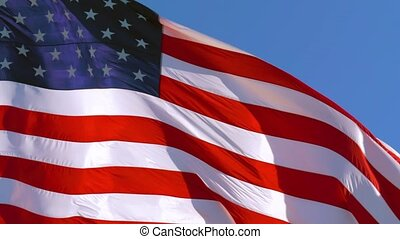 American flag of the USA flutters in the wind against a clear blue sky on a sunny day. Close Up, 4K video