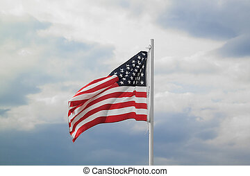 American flag on a blue sky with clouds background