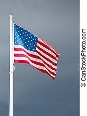 American flag on dark stormy sky