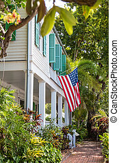American Flag on Green Shuttered House