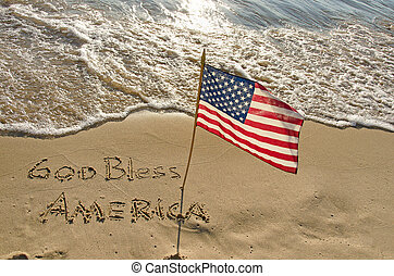 American flag in beach sand with holiday greeting.
