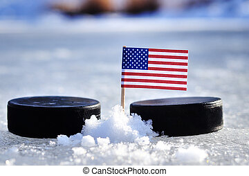 American flag on toothpick between two hockey pucks. Winter classic. Flag on frozen pond on unkempt ice. Traditional pucks for international matches.