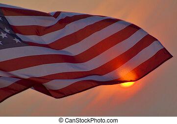 American Flag - An American flag against a setting sun.