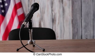 American flag, table and microphone. Banner behind desk with...