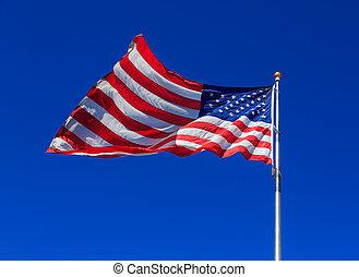 American flag waving in clear blue sky