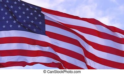 American Flag Waving In The United States Of America Shows Independence. National Patriotism And Celebration With Banner Flying. American Flag blowing in the wind with a blue sky background. 4K video.