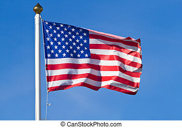 American flag waving on blue sky