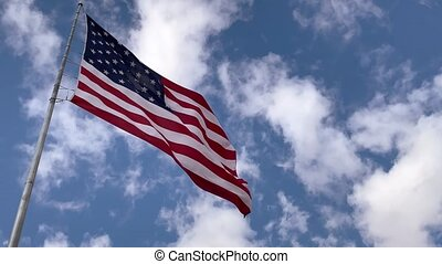 American Flag Waving on Wind With Clouds and Sky in Background, Close Up