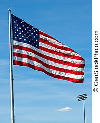 American Flag Waving Proudly on a Clear Windy Day at a Stadium